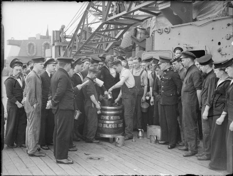 Sailors cueing to receive their rum tot from teh gog tub aboard the the RFA Bacchus (A103), a stores freighter and distilling ship during WWII - c/o Imperial War Museum